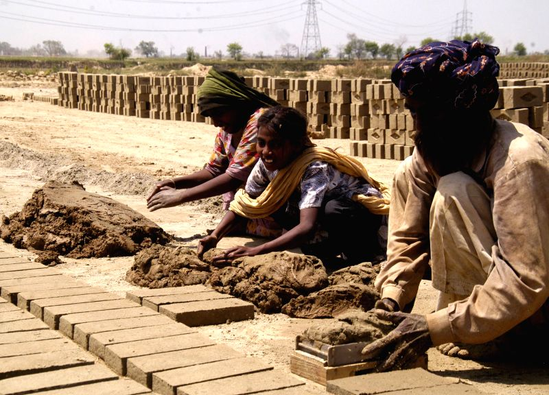 Pakistani laborers work at a brick factory on the eve of International Labor Day in eastern Pakistan??s Lahore on April 30, 2014. Pakistan has a workforce of around