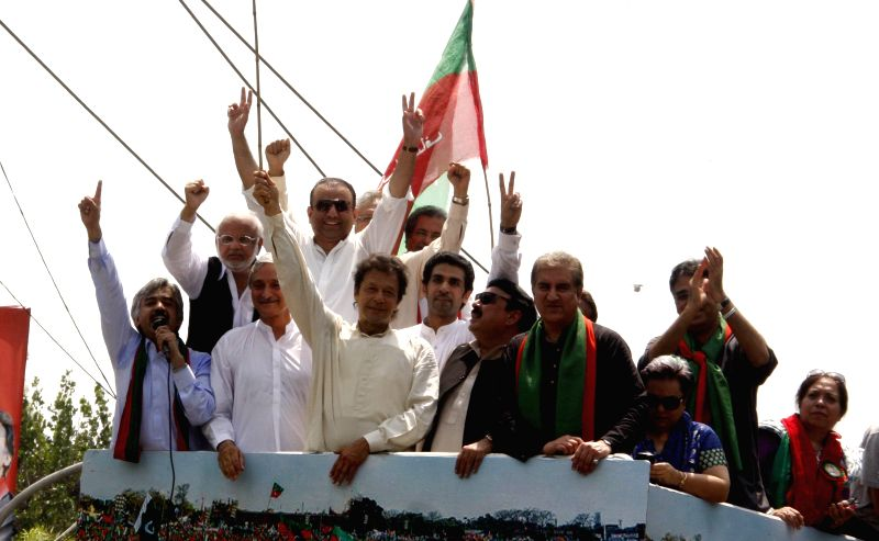 Pakistan senior opposition leader Imran Khan (C) gestures as he heads a protest march from Lahore to Islamabad against the government, in east Pakistan's Lahore on .. - Imran Khan