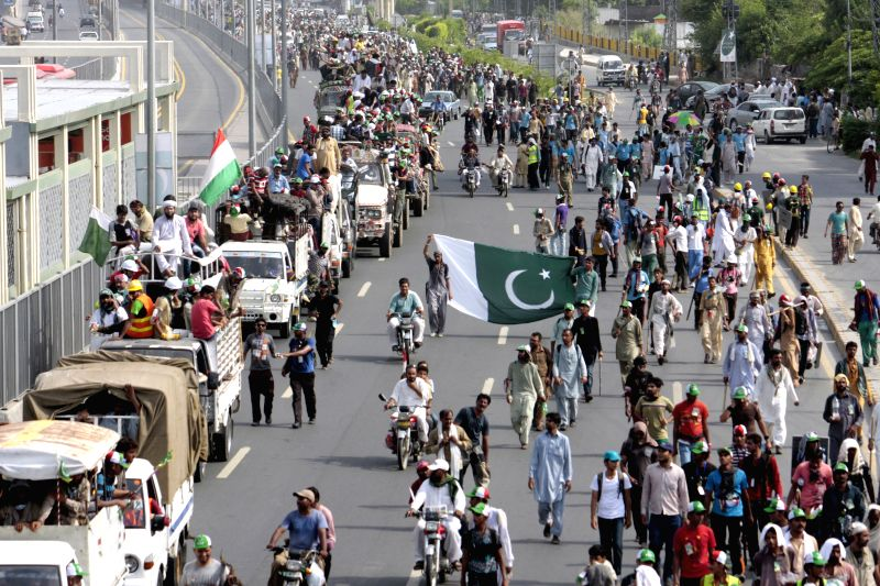 Supporters of anti-government cleric Tahir-ul-Qadri march on a street in eastern Pakistan's Lahore on Aug. 14, 2014. Thousands of Pakistani people, escorting ...