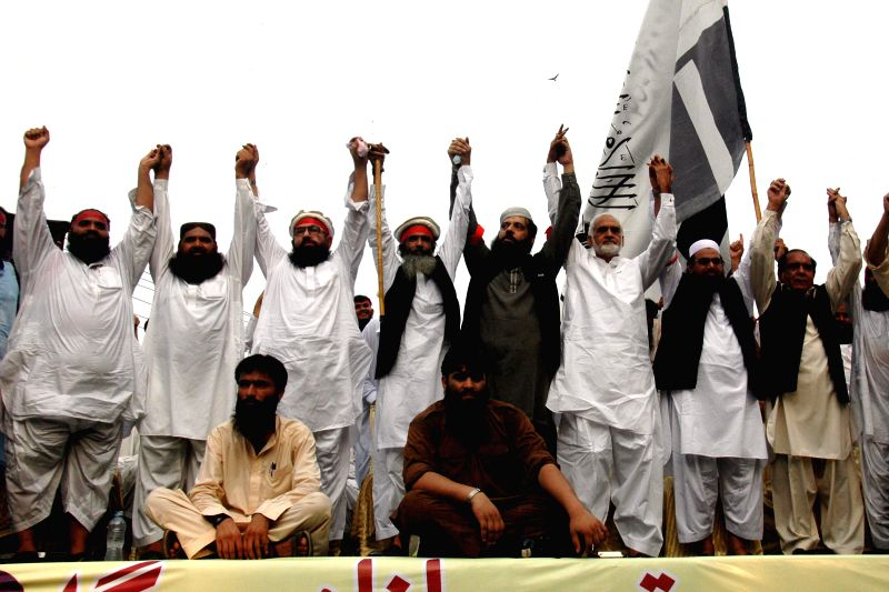 Pakistani leaders from various religious parties join hands and gesture towards supporters during a rally against the Israeli air strike on the Gaza Strip, in eastern