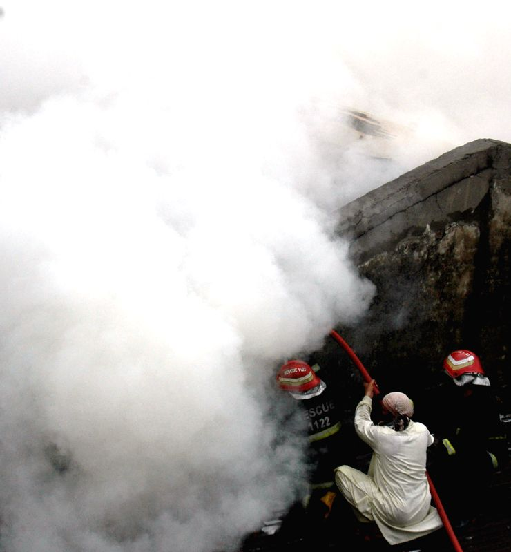 Fire fighters try to extinguish the fire in eastern Pakistan's Lahore on Aug. 4, 2014. A fire erupted at an auto market in Lahore on Monday, local media reported. ...