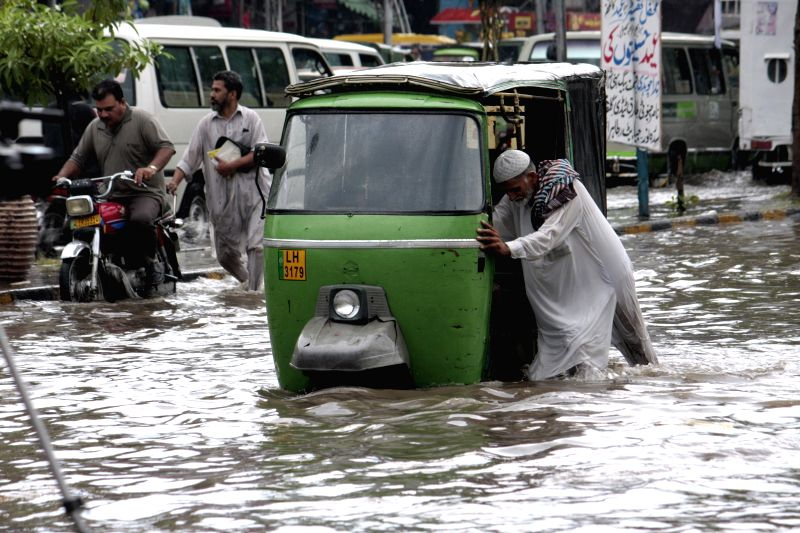 A Pakistani man pushes his auto-rickshaw in a flooded street after heavy monsoon rain in eastern Pakistan's Lahore on Aug. 9, 2014.