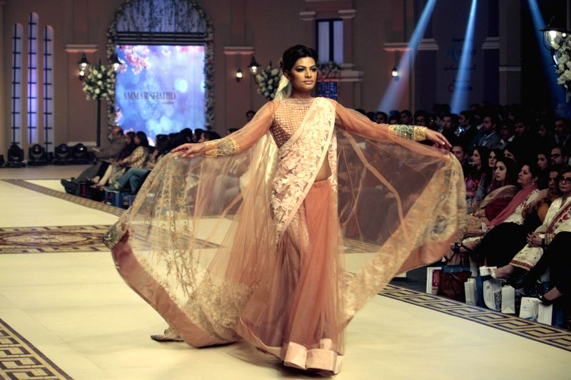 A model presents a creation designed by Ammar Shahid on the second day of Bridal Couture Fashion Week in eastern Pakistan's Lahore on Dec. 12, 2014. (Xinhua/Jamil ...