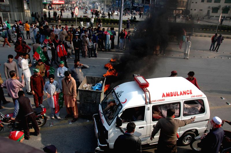 An ambulance moves as activists of Pakistan Tehreek-e-Insaf (PTI) party block a road during an anti-government protest in eastern Pakistan's Lahore on Dec. 15, 2014. - Imran Khan
