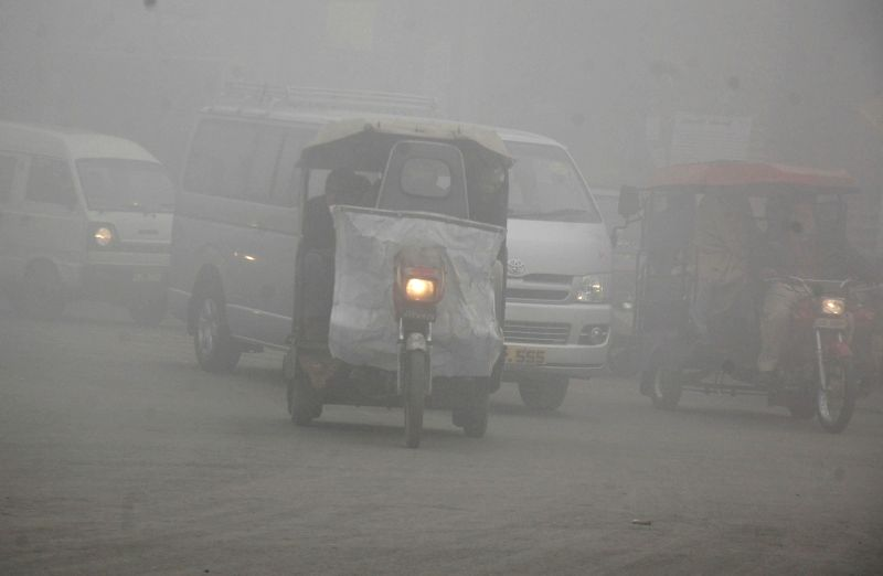 LAHORE, Dec. 30, 2014 (Xinhua) -- Vehicles move on road during a foggy morning in eastern Pakistan's Lahore on Dec. 30, 2014. The ongoing spell of dense fog and freezing weather conditions has continued to disturb the scheduled arrival and departure