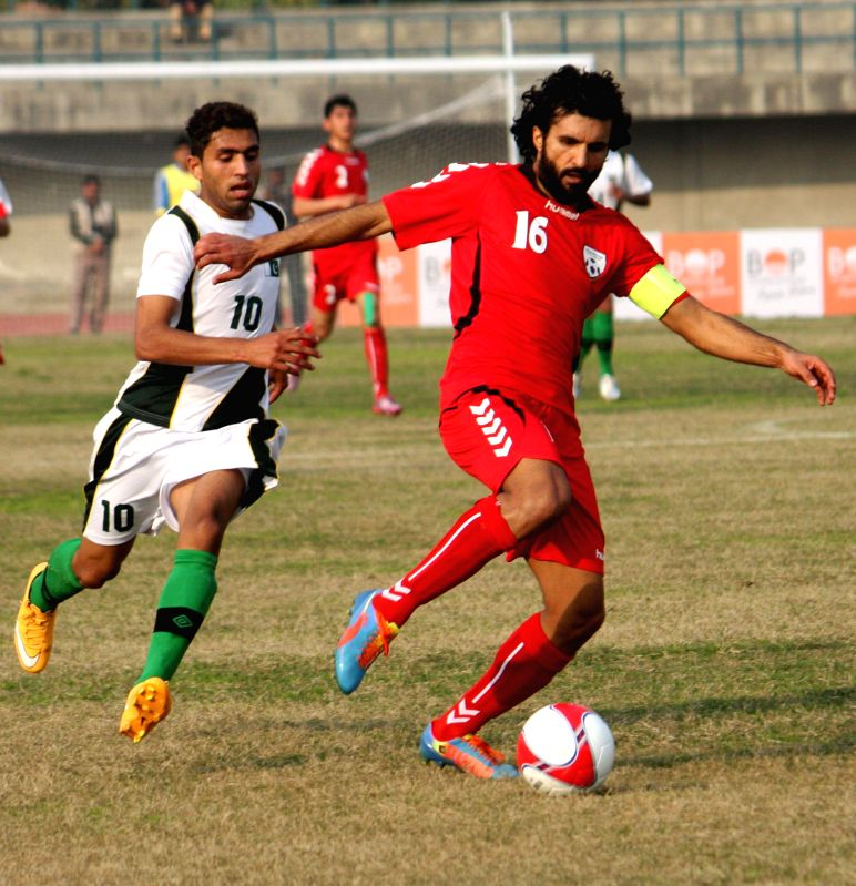 Afghanistan's Rehman (R) vies with Pakistan's Mohsin Raza during a friendly soccer match between Pakistan and Afghanistan in eastern Pakistan's Lahore, Feb. 6, 2015. .
