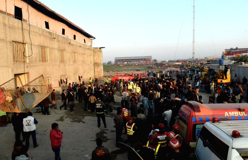 LAHORE, Jan. 11, 2017 - Rescuers gather outside the fire site in eastern Pakistan's Lahore on Jan. 11, 2017. At least seven people were killed and eight injured when a building caught fire near ...