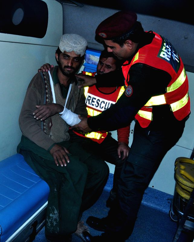 LAHORE, Jan. 11, 2017 - Rescuers help an injured man after a fire in eastern Pakistan's Lahore on Jan. 11, 2017. At least seven people were killed and eight injured when a building caught fire near ...