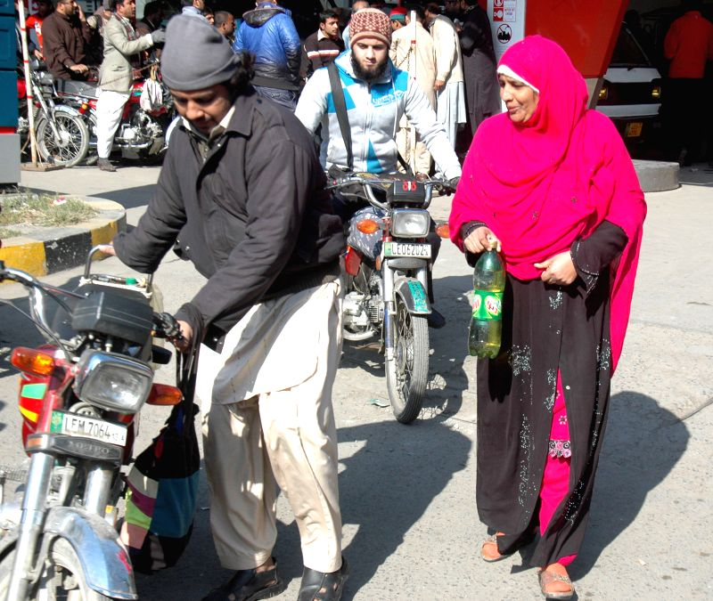 A man pushes his motorbike at a fuel station in east Pakistan's Lahore, Jan. 16, 2015. Shortage of petrol continued on the fourth day in various areas of Punjab ...