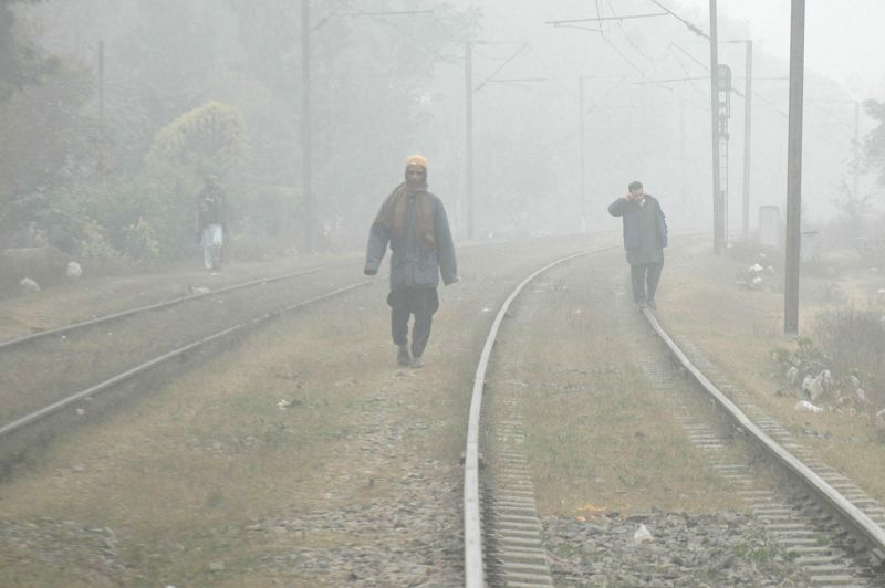 People walk on railway tracks during foggy morning in eastern Pakistan's Lahore, Jan. 18, 2015.