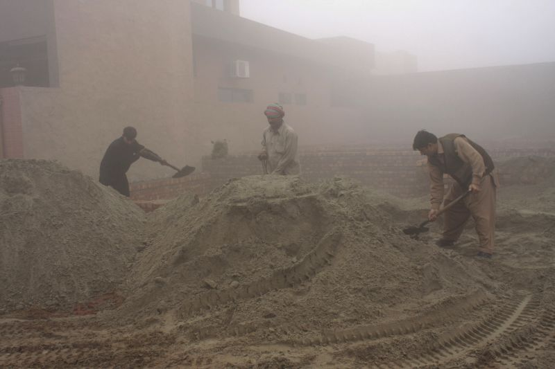 Pakistani laborers work at a construction site on a cold and foggy morning in eastern Pakistan's Lahor, Jan. 2, 2015.
