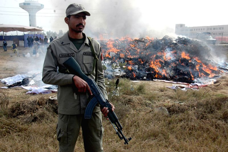 A Pakistani soldier stands guard beside burning drugs and liquor during a ceremony marking International Customs Day in Lahore, Pakistan, on Jan. 26, 2015. ...