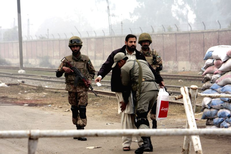 Pakistani soldiers check a man outside the Kot Lakhpat Central jail in eastern Pakistan's Lahore, Jan. 8, 2015. Security upgraded to high alert after the lifting of a