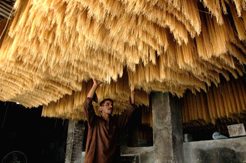 A man checks the quality of dried noodles at a local factory in east Pakistan's Lahore on July 16, 2014. Many Pakistani people buy noodles for an early morning meal .