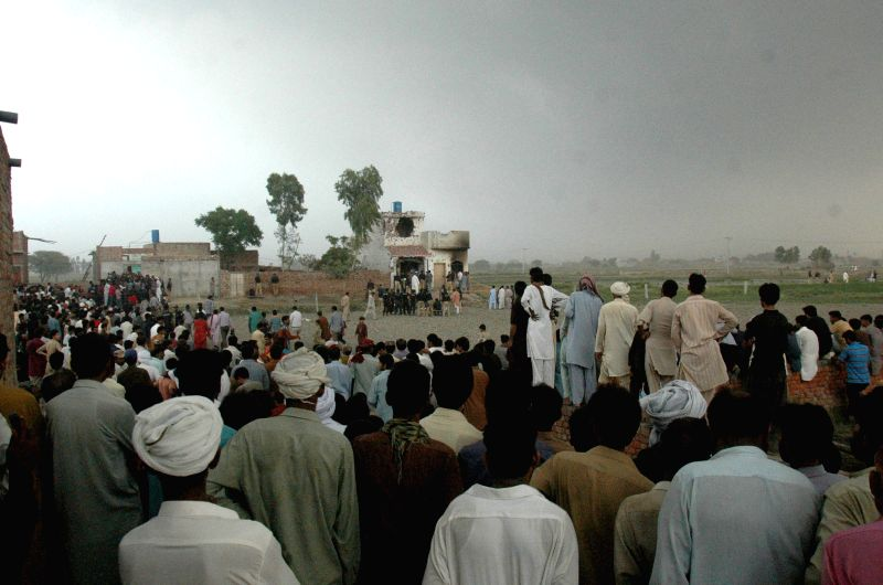 Locals gather at the clash site between security forces and militants on the outskirts of Lahore, eastern Pakistan, on July 17, 2014. A miscreant and a policeman ...