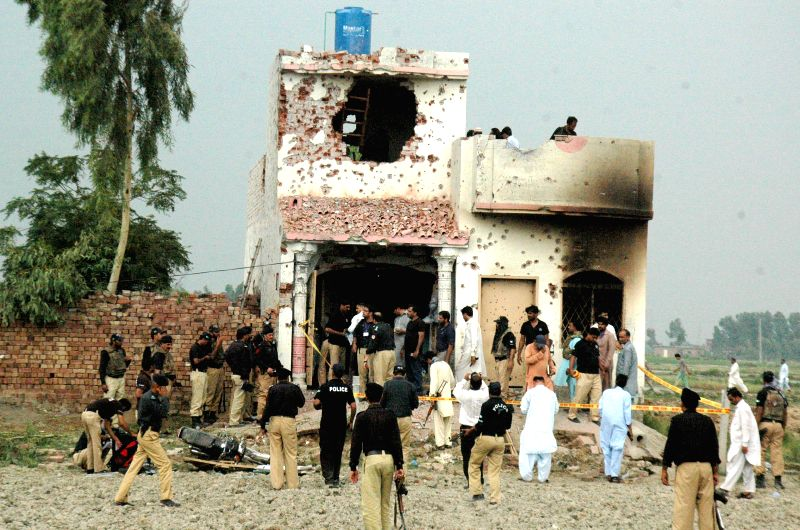 Policemen inspect a damaged building after a clash between security forces and militants on the outskirts of Lahore, eastern Pakistan, on July 17, 2014. A miscreant .