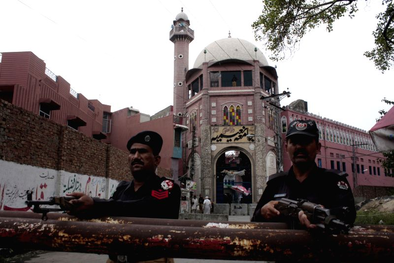 Pakistani policemen stand guard outside a mosque during the holy month of Ramadan at Badshahi Mosque in eastern Pakistan's Lahore on July 24, 2014. (Xinhua/Jamil ...