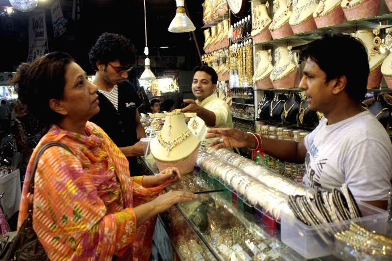 A Pakistani woman buys jewelry at a shop ahead of the Eid al-Fitr in eastern Pakistan's Lahore on July 27, 2014.
