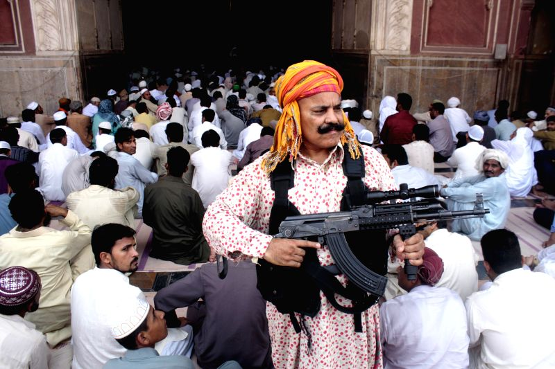 A private security guard stands alert as Pakistani Muslims offer Friday prayer at the first week the holy month of Ramadan at Badshahi Mosque in eastern Pakistan's ...