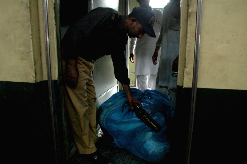A policeman scans luggages at a railway station due to security high alert in eastern Pakistan's Lahore, July 9, 2014. Security tightened in Lahore railway station on
