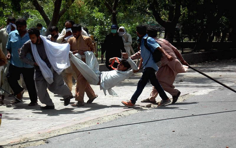 Pakistan Awami Tehreek (PAT) protestors carry an injured man during clashes with police in east Pakistan's Lahore on June 17, 2014. At least seven protestors, ...