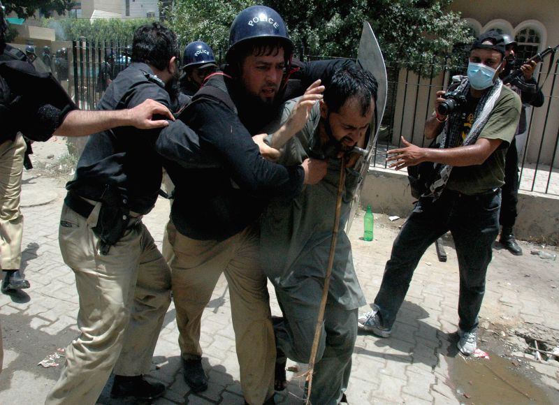 Policemen arrest a man during clashes with Pakistan Awami Tehreek (PAT) protestors in east Pakistan's Lahore on June 17, 2014. At least seven protestors, including ..