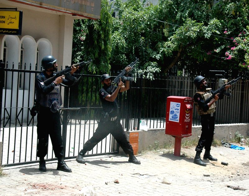 Policemen stand guard during clashes with Pakistan Awami Tehreek (PAT) protestors in east Pakistan's Lahore on June 17, 2014. At least seven protestors, including ...