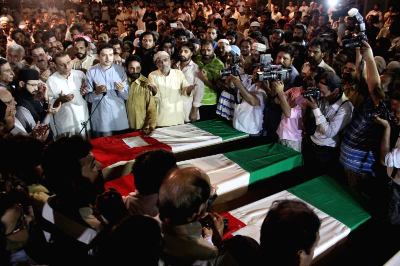 People attend a funeral ceremony for supporters of Pakistan Awami Tehreek (PAT) who were killed in the clashes in eastern Pakistan's Lahore, June 17, 2014. At least .