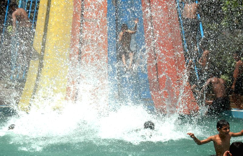 Pakistani children play on a water slide in a swimming pool to cool off during heat wave in east Pakistan's Lahore, June 22, 2014.