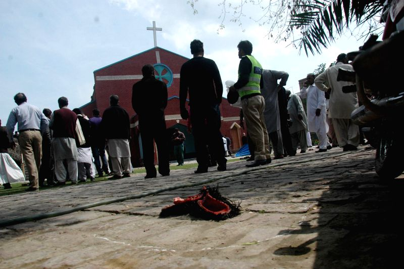 People gather outside a church at the blast site in eastern Pakistan's Lahore on March 15, 2015. At least 10 people were killed and 48 others wounded when two ...