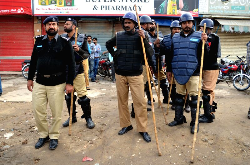 Pakistani policemen carry bamboo sticks during a protest by Christians mourners in eastern Pakistan's Lahore, March 16, 2015. At least four people were killed and ...