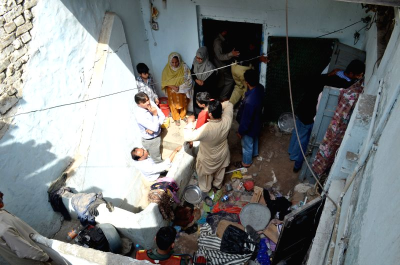 People gather at the accident site in eastern Pakistan's Lahore, March 24, 2015. At least three people were killed as a residential building in downtown Lahore ...