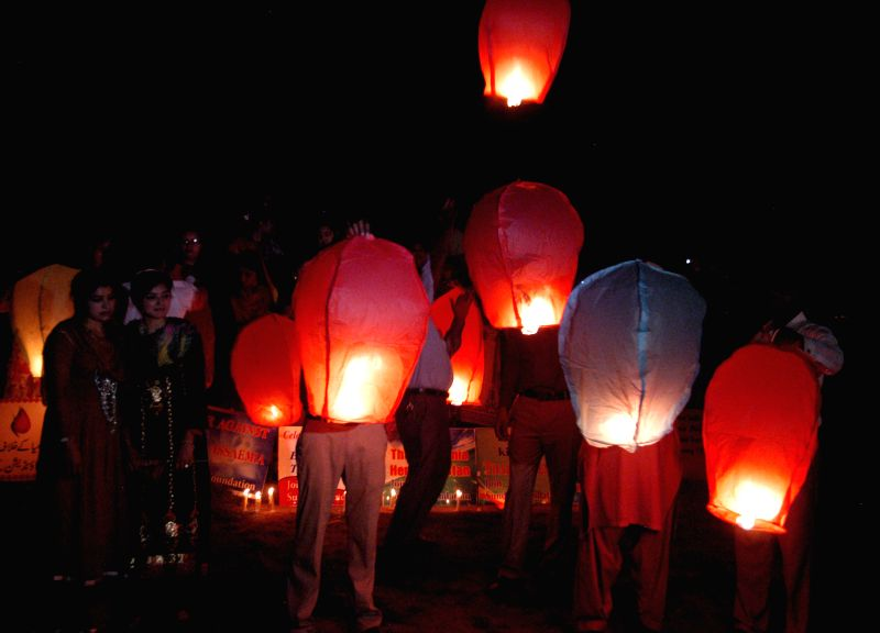 Pakistani people launch sky lanterns during a ceremony to mark the International Thalassemia Day in eastern Pakistan's Lahore, May 7, 2014. Thalassemia is a genetic ...