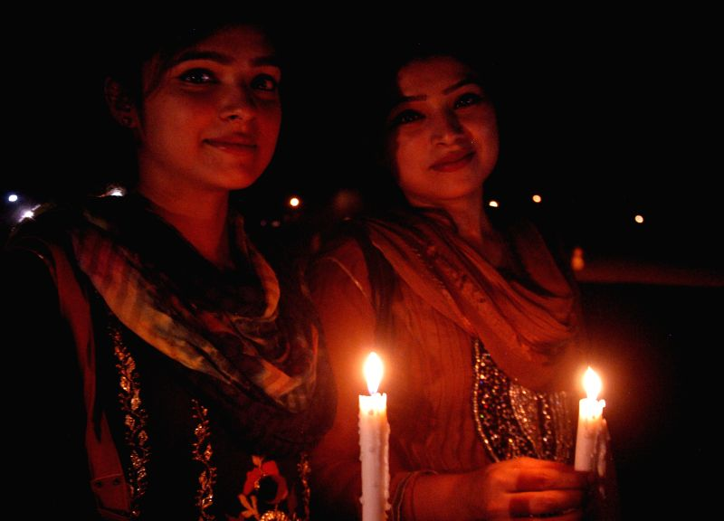 Pakistani women hold candles during a ceremony to mark the International Thalassemia Day in eastern Pakistan's Lahore, May 7, 2014. Thalassemia is a genetic disease of