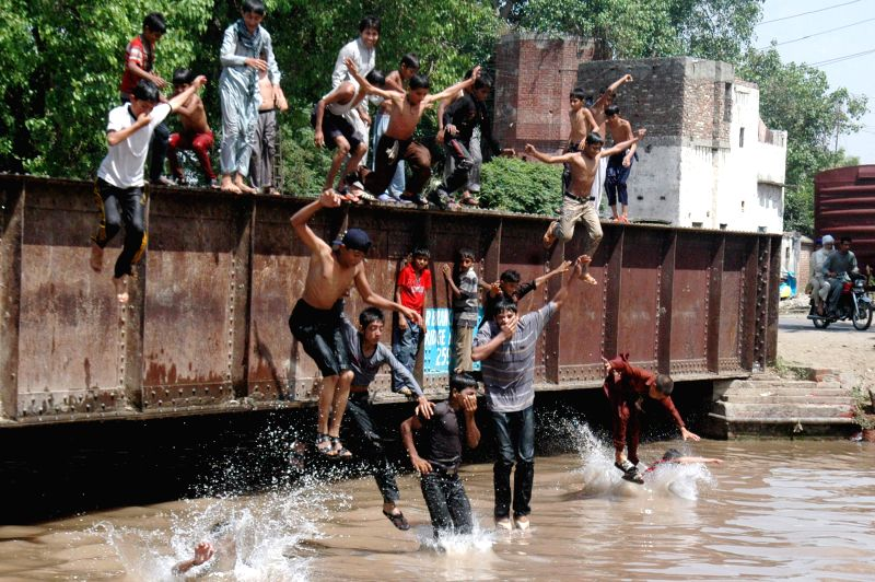 Pakistani boys jump into a canal to cool off themselves during heat wave in eastern Pakistan's Lahore, on May 9, 2015. Temperatures reach over 45 degrees Celsius in ...