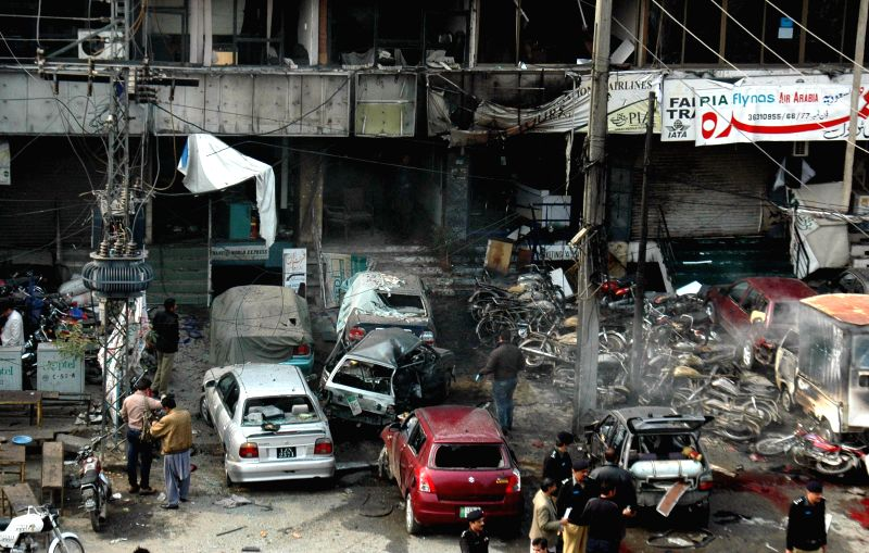 Policemen inspect the suicide attack site in eastern Pakistan's Lahore, Feb. 17, 2015. At least eight persons were killed and 12 others injured on Tuesday afternoon in a suicide blast outside