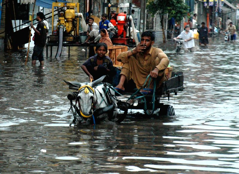 Pakistani laborers ride on a donkey-cart into a flooded street after heavy rain in east Pakistan's Lahore on Sept. 1, 2014.  ****Authorized by ...