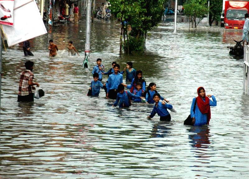 Pakistani students cross a flooded street after heavy rain in east Pakistan's Lahore on Sept. 1, 2014.