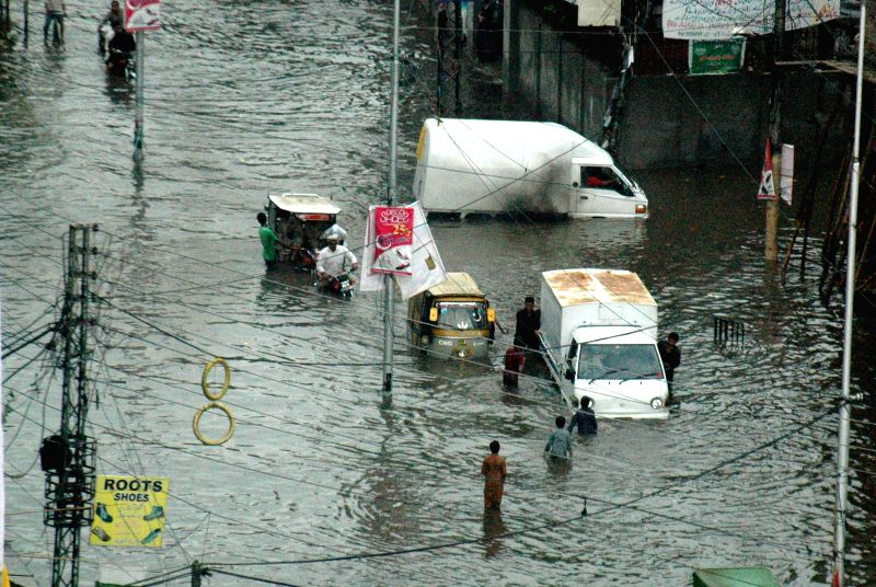 Vehicles drive on a flooded street after heavy rain in east Pakistan's Lahore on Sept. 1, 2014.