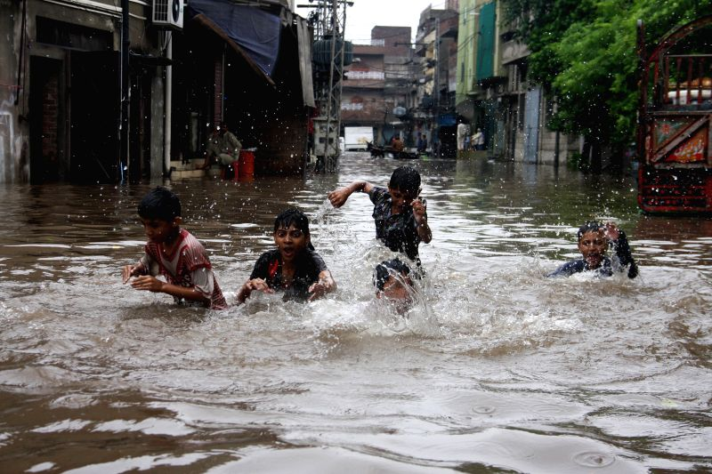 Children walk on the flooded street in eastern Pakistan's Lahore, Sept. 4, 2014. At least 40 people were killed and dozens others injured in separate accidents ...