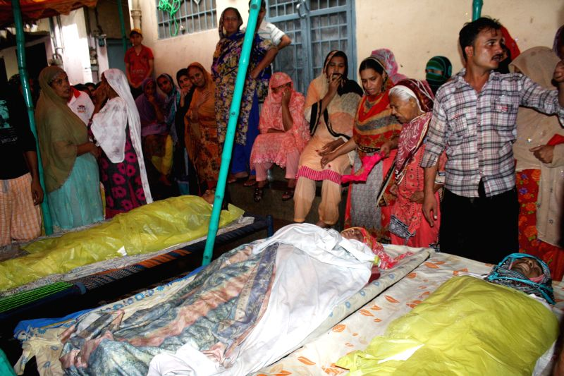 People gather around bodies killed in rain related accident in eastern Pakistan's Lahore on Sept. 4, 2014. At least 18 people were killed and 26 others injured in ...