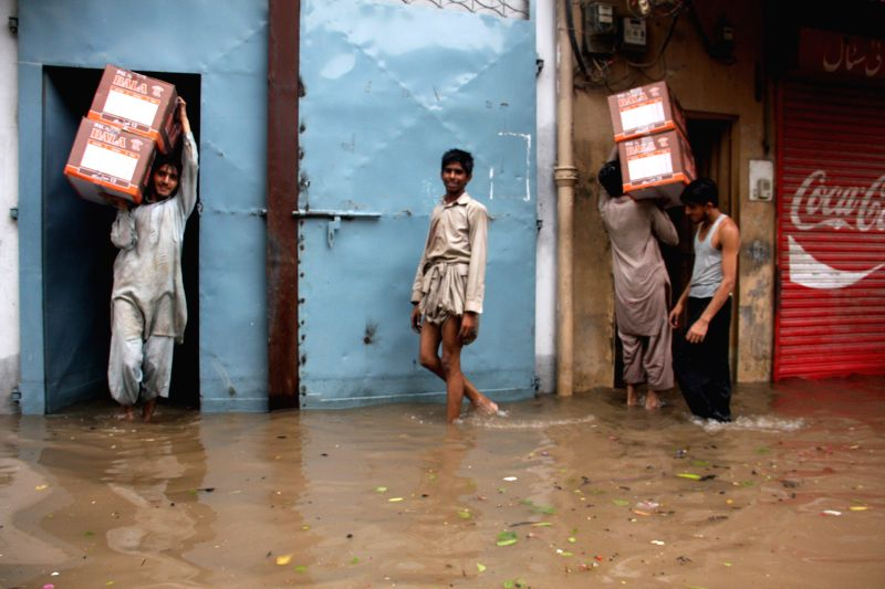 People walk on the flooded street in eastern Pakistan's Lahore, Sept. 4, 2014. At least 40 people were killed and dozens others injured in separate accidents ...