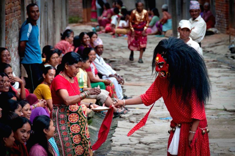 A woman offers money to a Newari in traditional costume performing Lakhey dance at Khokana in Lalitpur, Nepal, Aug. 12, 2014. The Lakhey dance is performed mainly .