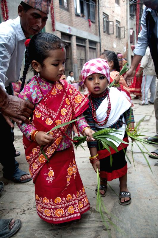 Newari girls participate in the ropai jatra to remember their late relations and for better paddy and also for fun at Khokana in Lalitpur, Nepal, Aug. 12, 2014. ...