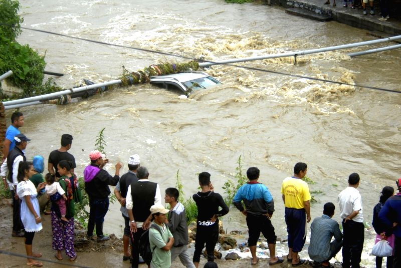 LALITPUR, Aug. 6, 2018 - People look at a drowning car being washed away by the swollen Godawari river following torrential rains in Lalitpur, Nepal, Aug. 6, 2018.