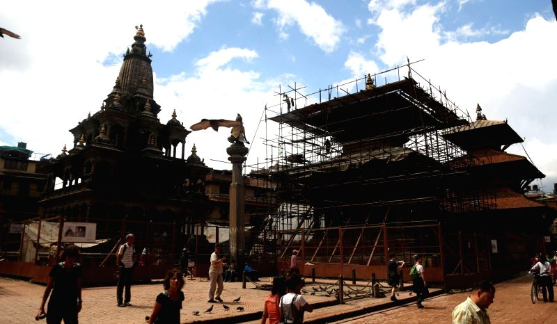 LALITPUR, July 26, 2018 - People walk around the reconstruction site of Patan Durbar Square in Lalitpur, Nepal, on July 25, 2018. Reconstruction process is undergoing in Patan Durbar Square as many ...