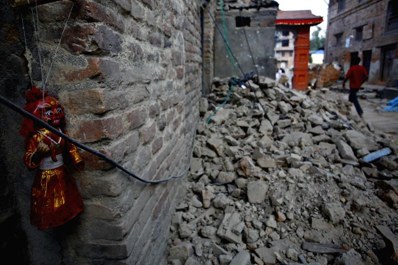 A traditional souvenir of Lakhey is seen on a damaged house in Lalitpur, Nepal, May 4, 2015. The death toll of Nepal's April 25 earthquake has risen to 7,365, with ...