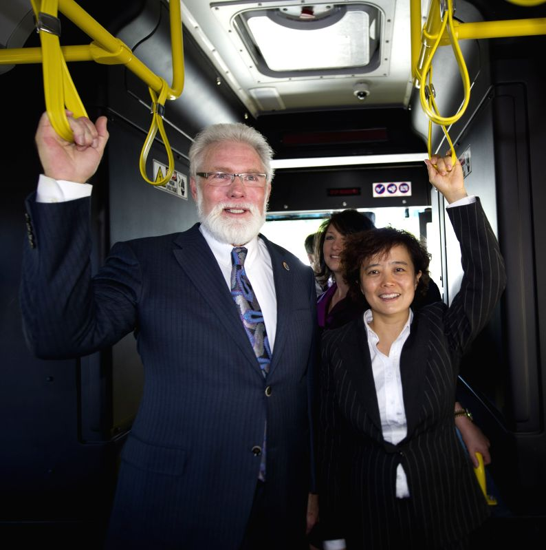 Lancaster Mayor Rex Parris and BYD Senior Vice President Li Ke (R) pose for pictures in the first American-made electric bus built at BYD's factory in Lancaster,