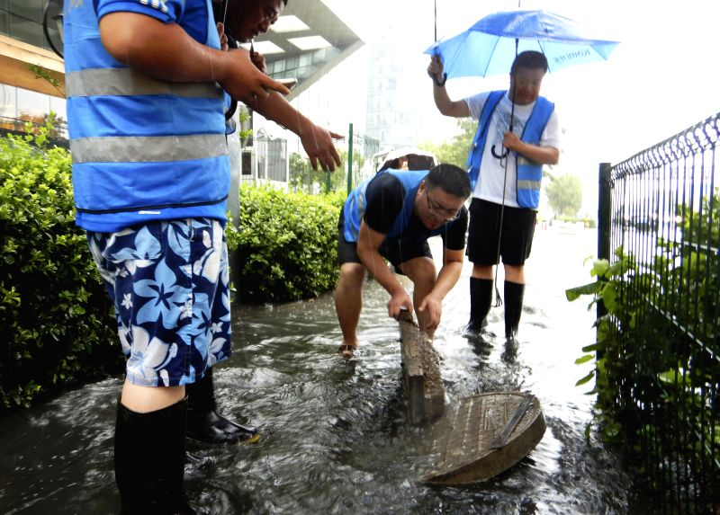 LANGFANG, July 24, 2018 - Workers from the municipal administration check sewers in Langfang, north China's Hebei Province, July 24, 2018. Heavy downpours brought by Typhoon Ampil pounded Beijing and ...