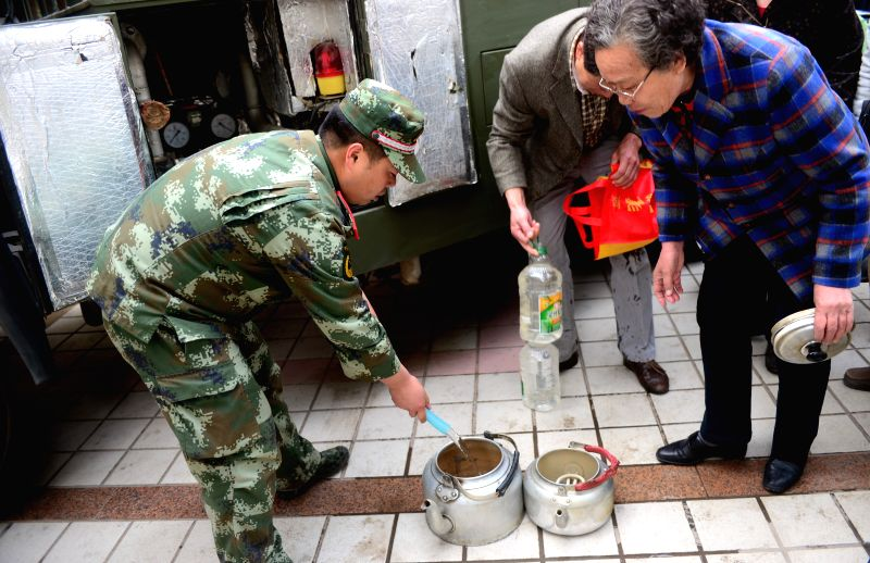 Local residents get water in a community in Lanzhou, capital of northwest China's Gansu Province, April 12, 2014. Tap water in downtown Lanzhou has been found to ..